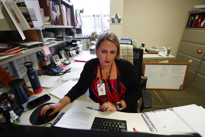 "Jennifer Gottschalk, environmental health supervisor of the Toledo-Lucas County Health Department, works in her office in Toledo, Ohio, on Wednesday, June 24, 2020. ""Being yelled at by residents for almost two hours straight last week on regulations I cannot control left me feeling completely burned out,"" she said in mid-June. (AP Photo/Paul Sancya)"