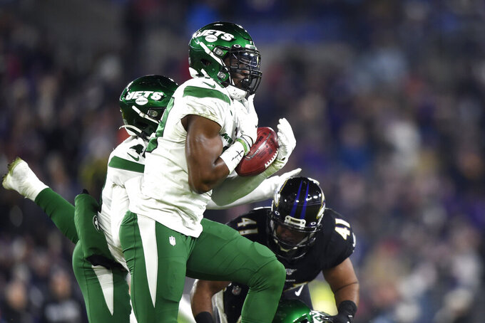 New York Jets linebacker B.J. Bello catches a blocked punt before returning it for a touchdown against the Baltimore Ravens during the second half of an NFL football game, Thursday, Dec. 12, 2019, in Baltimore. (AP Photo/Gail Burton)