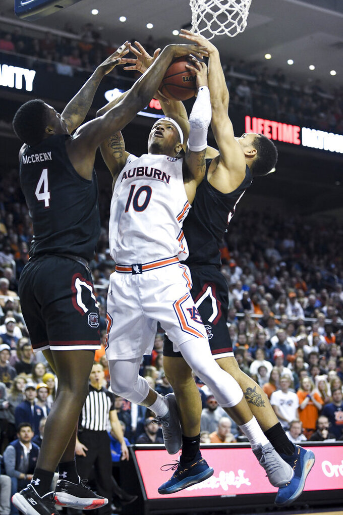 South Carolina forward Jalyn McCreary (4) and South Carolina guard Jair Bolden (52) block a shot by Auburn guard Samir Doughty (10) during the second half of an NCAA college basketball game Wednesday, Jan. 22, 2020, in Auburn, Ala. (AP Photo/Julie Bennett)