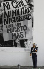 A soldier stands guard next to a giant poster that reads in Spanish