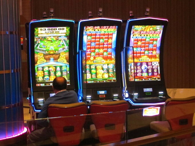 This May 3, 2021 photo shows a man playing a slot machine at the Hard Rock casino in Atlantic City, N.J. On Thursday, June 3, 2021, New Jersey legislators were scheduled to vote on four bills giving relief to the Atlantic City casino industry following coronavirus-related declines, and to expand some other forms of gambling. (AP Photo/Wayne Parry)