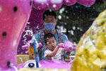A man wearing a mask to curb the spread of the new coronavirus and a child who temporarily removed his to enjoy a ride at a local park in Beijing on Saturday, May 23, 2020. New coronavirus cases dropped to zero in China for the first time Saturday but overwhelmed hospitals across Latin America – both in countries lax about lockdowns and those lauded for firm, early confinement. (AP Photo/Ng Han Guan)