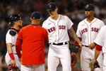 Boston Red Sox's Tanner Houck, center, hands the ball to manager Alex Cora, second from left, as he is taken out during the fifth inning of a baseball game against the Minnesota Twins, Tuesday, Aug. 24, 2021, in Boston. (AP Photo/Michael Dwyer)