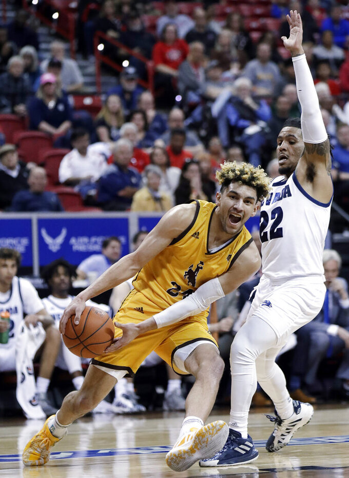 Wyoming's Hunter Maldonado drives under the basket as Nevada's Jazz Johnson defends during the first half of a Mountain West Conference tournament NCAA college basketball game Thursday, March 5, 2020, in Las Vegas. (AP Photo/Isaac Brekken)