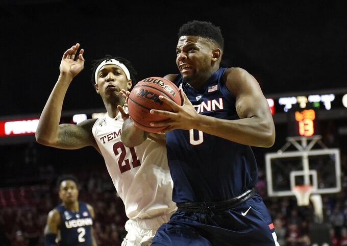 Connecticut's Eric Cobb (0) drives the ball to the basket against Temple's  Justyn Hamilton (21) during the first half of an  NCAA college basketball game, Wednesday, Feb. 6, 2019, in Philadelphia. (AP Photo/Michael Perez)