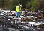 A worker with the environmental clean up company AAG Environmental works to remove fuel spilled at the scene of Thursday's multi-vehicle accident that caused multiple fatalities on Interstate 75 between Alachua and Gainesville, Fla., on Friday, Jan. 4, 2019. (Brad McClenny/The Gainesville Sun via AP)