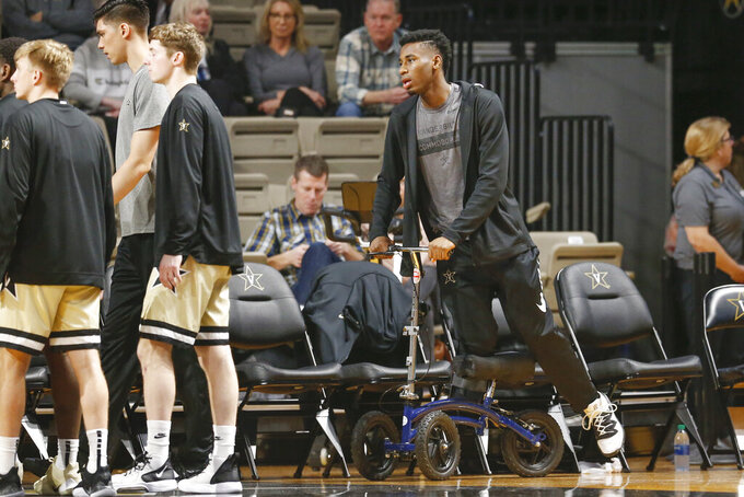 Injured Vanderbilt sophomore guard Aaron Nesmith uses a scooter and a walking boot as he watches his teammates play Texas A&M in an NCAA college basketball game Saturday, Jan. 11, 2020, in Nashville, Tenn. Nesmith is the SEC's leading scorer and fifth nationally averaging 23 points a game. Texas A&M won 69-50. (AP Photo/Mark Humphrey)