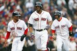 Boston Red Sox's Xander Bogaerts, center, celebrates his three-run home run that also drove in Mookie Betts, left, and J.D. Martinez, right, during the eighth inning of a baseball game against the Baltimore Orioles in Boston, Sunday, April 14, 2019. (AP Photo/Michael Dwyer)
