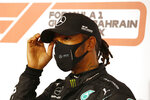 FILE - In this Saturday, Nov. 28, 2020 file photo Mercedes driver Lewis Hamilton of Britain gestures after taking the pole position after the qualifying session at the Formula One Bahrain International Circuit in Sakhir, Bahrain. World champion Lewis Hamilton tested positive for COVID-19 and will miss the Sakhir Grand Prix this weekend, his Mercedes-AMG Petronas F1 Team said Tuesday Dec. 1, 2020. (Hamad Mohammed, Pool via AP, File)