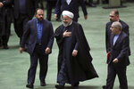 Iranian President Hassan Rouhani, center, leaves the parliament after submitting next year's budget bill as he is accompanied by Vice President for Parliamentary Affairs Hosseinali Amiri, left, and two other unidentified officials in Tehran, Iran, Sunday, Dec. 8, 2019. Rouhani said his country will depend less on oil revenue next year, in a new budget that is designed to resist crippling U.S. trade embargoes. (AP Photo/Vahid Salemi)