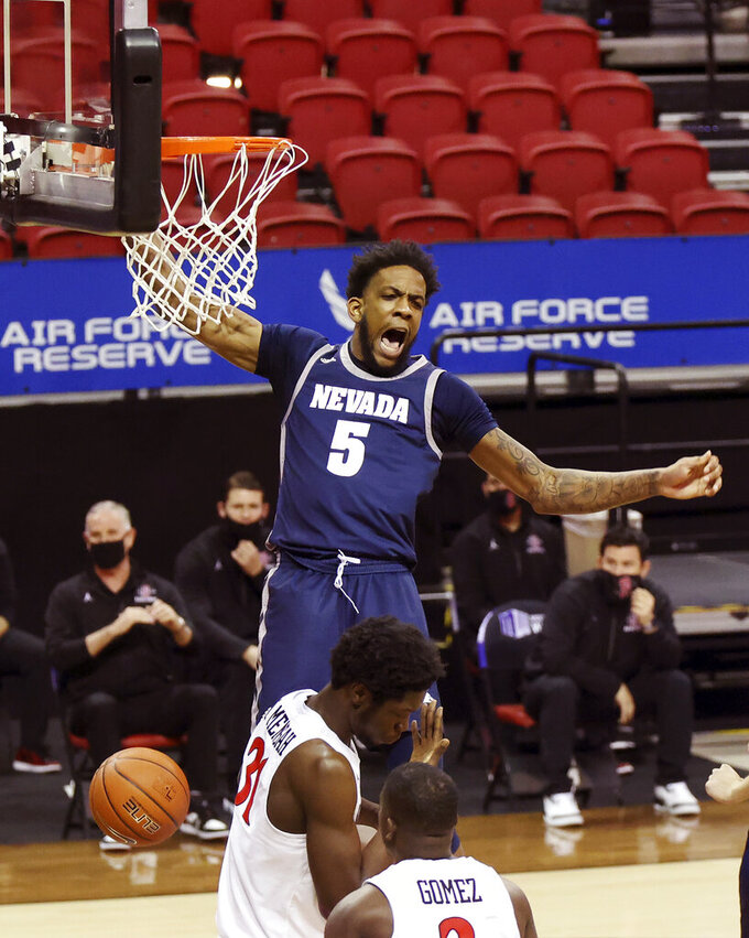 Nevada forward Warren Washington (5) reacts after dunking against San Diego State during the first half of an NCAA college basketball game in the semifinal round of the Mountain West Conference men's tournament Friday, March 12, 2021, in Las Vegas. (AP Photo/Isaac Brekken)