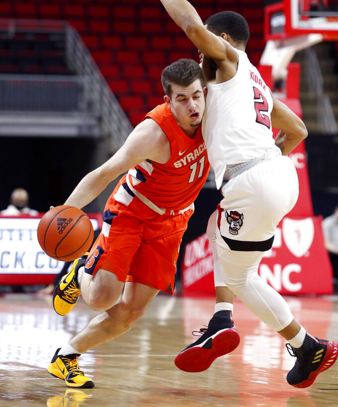 Syracuse's Joseph Girard III (11) drives around North Carolina State's Shakeel Moore (2) during the first half of an NCAA college basketball game, Tuesday, Feb. 9, 2021 in Raleigh, N.C. (Ethan Hyman/The News & Observer via AP, Pool)