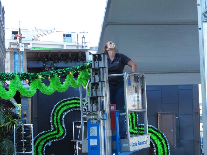 Sarah Hardilek uses a mechanical lift to hang green streamers for St. Patrick's Day at the Plant Riverside hotel and entertainment complex in Savannah, Ga., on Thursday, March 11, 2021. Savannah officials have cancelled the South's largest St. Patrick's Day parade for a second year because of the coronavirus. Regardless, big crowds are expected for the Irish holiday, raising concerns that Savannah's celebration could cause an outbreak. (AP Photo/Russ Bynum)