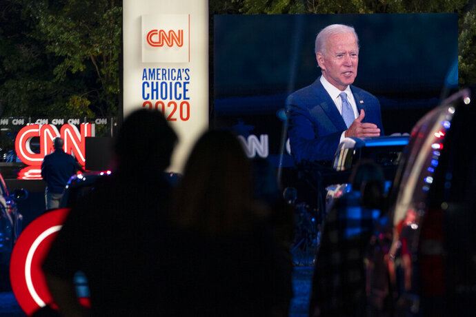 Audience members watch from their cars as Democratic presidential candidate former Vice President Joe Biden, seen on a monitor, speaks during a CNN town hall in Moosic, Pa., Thursday, Sept. 17, 2020. (AP Photo/Carolyn Kaster)