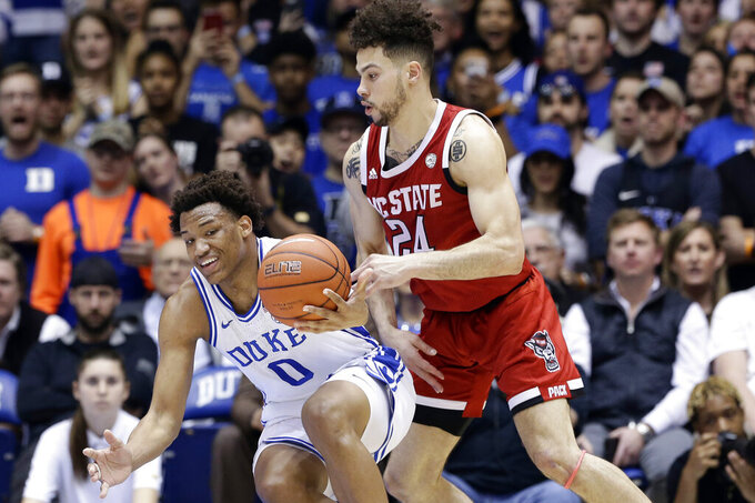 Duke forward Wendell Moore Jr. (0) reaches for the ball with North Carolina State guard Devon Daniels (24) during the first half of an NCAA college basketball game in Durham, N.C., Monday, March 2, 2020. (AP Photo/Gerry Broome)