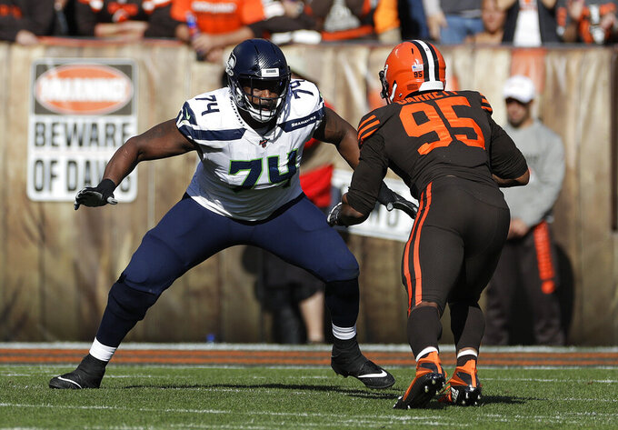 FILE - In this Oct. 13, 2019, file photo, Seattle Seahawks offensive tackle George Fant (74) plays against Cleveland Browns defensive end Myles Garrett (95) during the second half of an NFL football game in Cleveland. Fant, who is now with the New York Jets, spent most of his college days at Western Kentucky shooting basketballs and grabbing rebounds as a physical power forward with big-time hoop dreams. He had no idea then that football would ultimately be his path to stardom. (AP Photo/Ron Schwane, File)