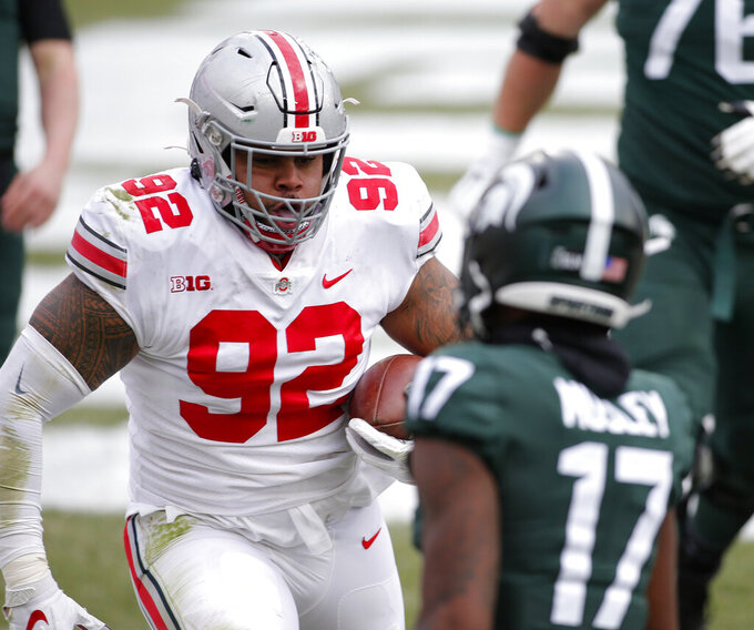 FILE - In this Dec. 5, 2020, file photo, Ohio State lineman Haskell Garrett, left, scores against Michigan State's Tre Mosley after deflecting and catching a Michigan State pass in the end zone during the first half of an NCAA college football game in East Lansing, Mich. Garrett was selected to The Associated Press Preseason All-America first team defense, Monday Aug. 23, 2021.(AP Photo/Al Goldis, File)