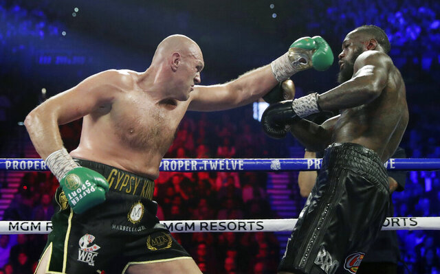 FILE - In this Feb. 22, 2020, file photo, Tyson Fury, left, of England, fights Deontay Wilder during a WBC heavyweight championship boxing match in Las Vegas. An all-British world heavyweight title showdown between Anthony Joshua and Tyson Fury in 2021 is a step closer. Fury said Wednesday, June 10, 2020, that an agreement has been reached with Joshua's camp on a two-fight deal between the current holders of the heavyweight belts.(AP Photo/Isaac Brekken, File)