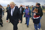 A member of the public, centre right, attempts to give Britain's Prime Minister Boris Johnson, foreground, a pro-EU leaflet as he campaigns on behalf of Conservative Party candidate Jill Mortimer, in Hartlepool, England, Monday, May 3, 2021, ahead of the 2021 Hartlepool by-election to be held on May 6. (Lindsey Parnaby/PA via AP)
