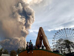 In this Sunday, Jan. 12, 2020, photo, people watch as the Taal volcano spews ash and smoke during an eruption in Tagaytay, Cavite province south of Manila, Philippines. (AP Photo/Bullit Marquez)