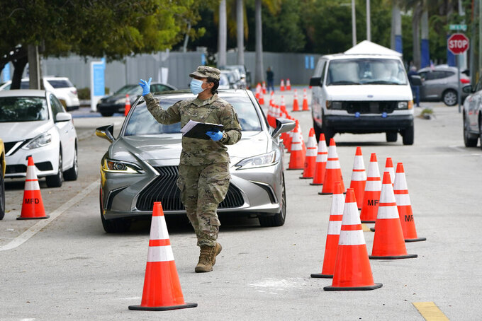 A member of the Florida National Guard directs vehicles at a drive-thru COVID-19 vaccination site at Marlins Park, Thursday, Jan. 21, 2021, in Miami. (AP Photo/Lynne Sladky)