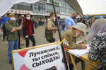 People, wearing face masks to protect against coronavirus, give their signatures in support of potential presidential candidates in the upcoming presidential elections in Minsk, Belarus, Sunday, June 7, 2020. The presidential campaign is underway in Belarus despite the coronavirus outbreak after the parliament and government refused to postpone the election scheduled for August 9. (AP Photo/Sergei Grits)