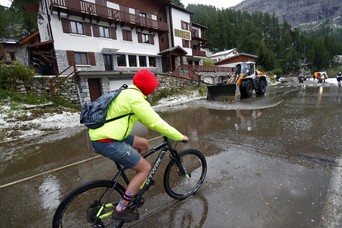 A supporter rides on a bicycle as a worker uses a digger to clean the road of the nineteenth stage of the Tour de France cycling race over 126,5 kilometers (78,60 miles) with start in Saint Jean De Maurienne and finish in Tignes, France, Friday, July 26, 2019. Tour de France organizers stopped Stage 19 of the race because of a hail storm as Julien Alaphilippe lost his yellow jersey to Egan Bernal. (AP Photo/Thibault Camus)