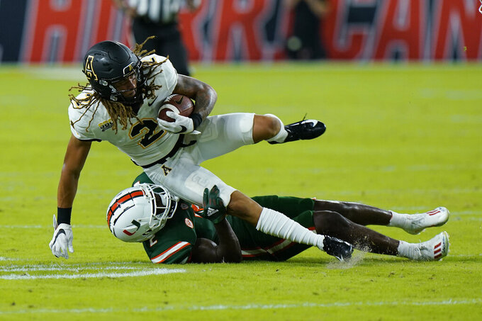 Appalachian State wide receiver Corey Xavier Sutton (2) is taken down by Miami cornerback Tyrique Stevenson during the first half of an NCAA college football game, Saturday, Sept. 11, 2021, in Miami Gardens, Fla. (AP Photo/Wilfredo Lee)