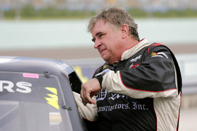 Joe Nemechek gets in his truck before practice for a NASCAR Truck Series auto race on Friday, Nov. 15, 2019, at Homestead-Miami Speedway in Homestead, Fla. Nemechek is expected to start his 1,186th race Friday, breaking Richard Petty's record of 1,185 for the most NASCAR starts. (AP Photo/Terry Renna)