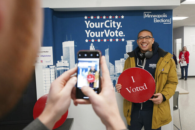 Jared Mollenkof has his photo taken after voting at the Minneapolis Early Voting Center, Friday, Jan. 17, 2020, in Minneapolis. Mollenkof and Davis Senseman arrived the night before so they could be among the first voters in the 2020 election, when the center opened at 8 a.m. They planned to vote for Democratic presidential candidate Elizabeth Warren in the state's primary. (Glen Stubbe/Star Tribune via AP)