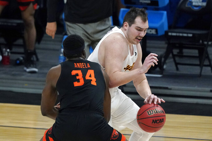 Loyola Chicago center Cameron Krutwig drives around Oregon State forward Rodrigue Andela (34) during the first half of a Sweet 16 game in the NCAA men's college basketball tournament at Bankers Life Fieldhouse, Saturday, March 27, 2021, in Indianapolis. (AP Photo/Jeff Roberson)