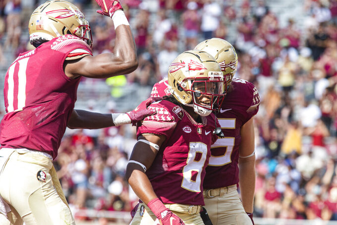 Florida State tight end Preston Daniel, right, and wide receiver Malik McClain, left, celebrate a touchdown by running back Treshaun Ward in the first half of an NCAA college football game against Louisville in Tallahassee, Fla., Saturday, Sept. 25, 2021. (AP Photo/Mark Wallheiser)