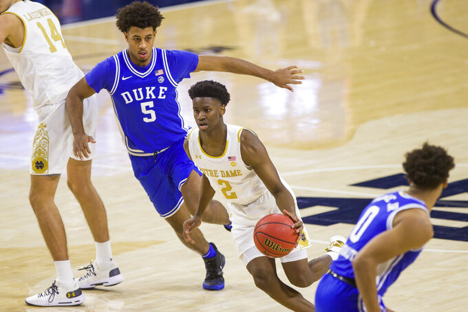 Notre Dame's Trey Wertz (2) drives between Duke's Jaemyn Brakefield (5) and Wendell Moore Jr. (0) during the second half of an NCAA college basketball game Wednesday, Dec. 16, 2020, in South Bend, Ind. Duke won 75-65. (AP Photo/Robert Franklin)
