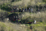 Investigators work the scene of a helicopter crash that killed former NBA basketball player Kobe Bryant, his 13-year-old daughter, Gianna, and several others Monday, Jan. 27, 2020, in Calabasas, Calif. (AP Photo/Mark J. Terrill)