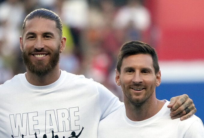 PSG's Lionel Messi, right, and PSG's Sergio Ramos smile during players presentation before the French League One soccer match between Paris Saint Germain and Strasbourg, at the Parc des Princes stadium in Paris, Saturday, Aug. 14, 2021. (AP Photo/Francois Mori)