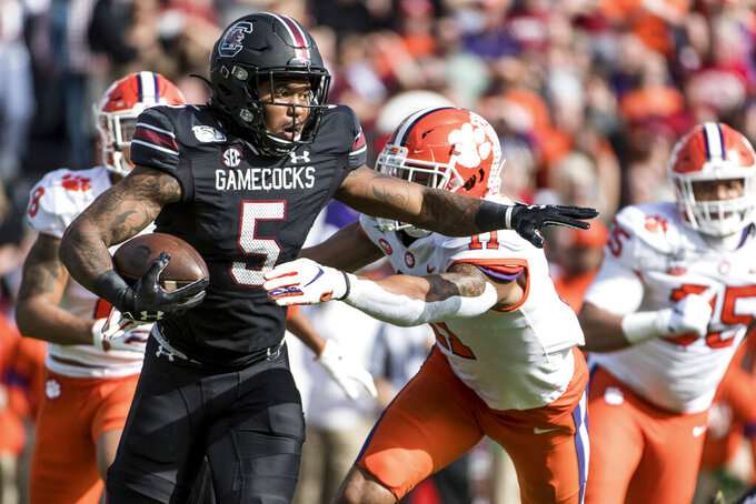 South Carolina running back Rico Dowdle (5) carries the ball against Clemson linebacker Isaiah Simmons (11) during the first half of an NCAA college football game Saturday, Nov. 30, 2019, in Columbia, S.C. (AP Photo/Sean Rayford)