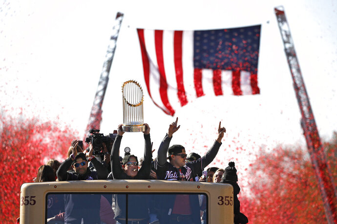Washington Nationals general manager Mike Rizzo holds up the World Series trophy during a parade to celebrate the team's World Series baseball championship over the Houston Astros, Saturday, Nov. 2, 2019, in Washington. (AP Photo/Patrick Semansky)