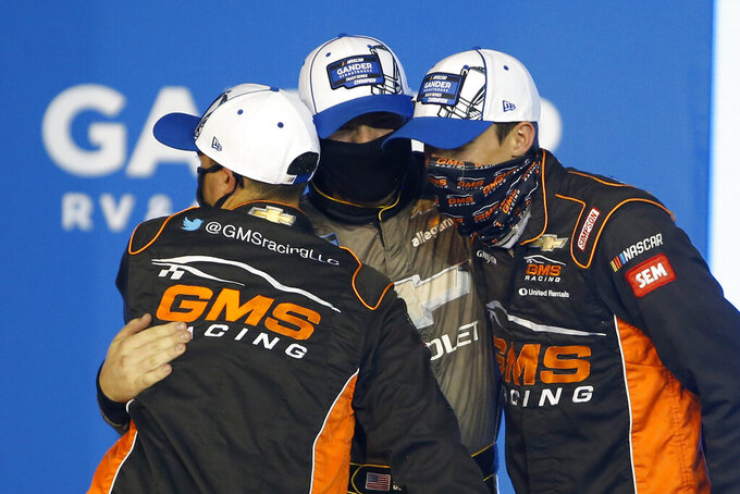 Driver Sheldon Creed, center, embraces crew members in victory lane after winning the season championship and the NASCAR Truck Series auto race at Phoenix Raceway, Friday, Nov. 6, 2020, in Avondale, Ariz. (AP Photo/Ralph Freso)