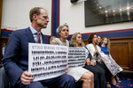 Michael Stumo and his wife Nadia Milleron, the parents of Samya Rose Stumo, hold up signs depicting those lost in Ethiopian Airlines Flight 302 and Lion Air Flight 610 during a House Committee on Transportation and Infrastructure hearing on the status of the Boeing 737 MAX on Capitol Hill in Washington, Wednesday, June 19, 2019. (AP Photo/Andrew Harnik)