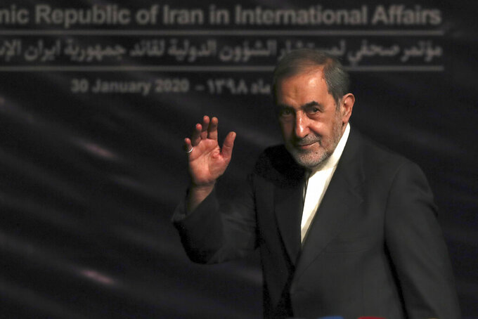 In this Jan. 30, 2020, photo, Ali Akbar Velayati, adviser to the Iranian supreme leader Ayatollah Ali Khamenei, waves to media at the conclusion of his press conference, in Tehran, Iran. In hard-hit Iran, state-run TV announced that Velayati was quarantined at home after testing positive for the virus. He is a close, trusted adviser to the 80-year-old leader of the Islamic Republic, who was recently seen wearing disposable gloves at a tree-planting ceremony, apparently out of caution about the virus. (AP Photo/Vahid Salemi)
