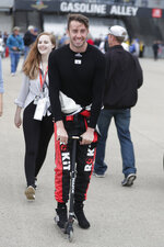 James Davison, of Australia, rides a scooter through the garage area practice for the Indianapolis 500 IndyCar auto race at Indianapolis Motor Speedway, Monday, May 20, 2019, in Indianapolis. (AP Photo/Michael Conroy)