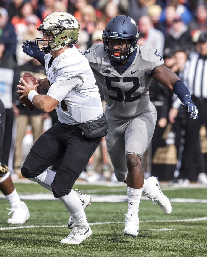 Purdue quarterback David Blough, left, is pursued by Illinois defensive end Ayo Shogbonyo (52) in the first half of an NCAA college football game, Saturday, Oct. 13, 2018, in Champaign, Ill. (AP Photo/Holly Hart)
