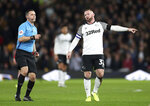 Derby County's Wayne Rooney talks with referee Dean Whitestone during the game against Barnsley, during their English Championship soccer match at Pride Park in Derby, England, Thursday Jan. 2, 2020. (Bradley Collyer/PA via AP)