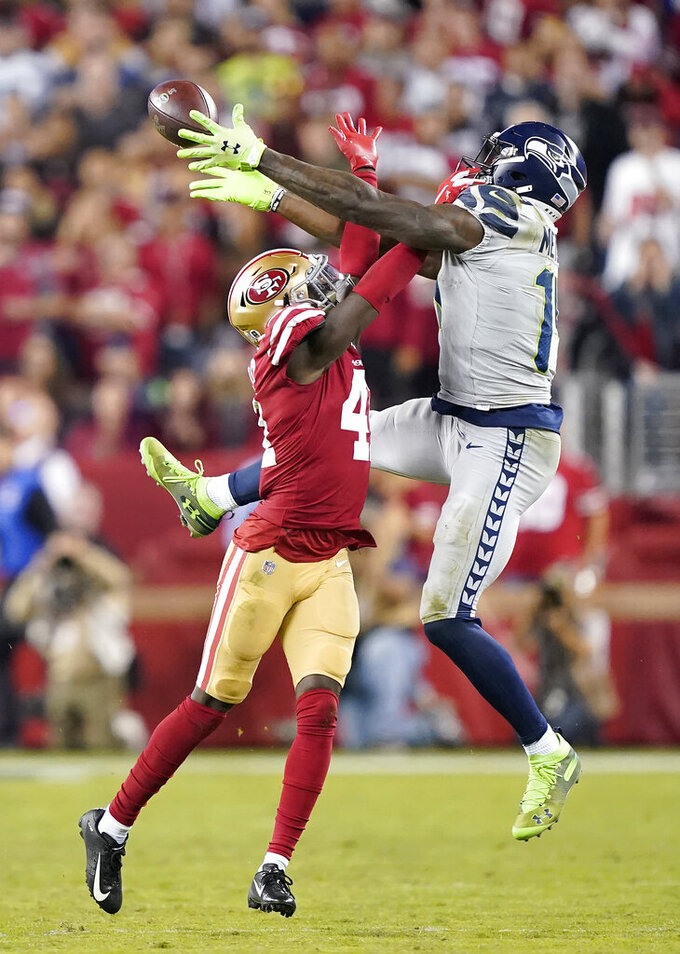 San Francisco 49ers defensive back Emmanuel Moseley, left, breaks up a pass intended for Seattle Seahawks wide receiver D.K. Metcalf during overtime of an NFL football game in Santa Clara, Calif., Monday, Nov. 11, 2019. (AP Photo/Tony Avelar)
