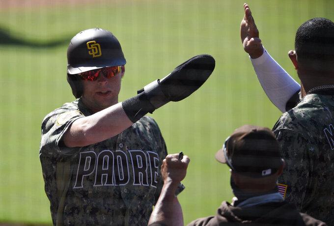 San Diego Padres' Jake Cronenworth is congratulated after scoring during the eighth inning of the team's baseball game against the Arizona Diamondbacks in San Diego, Sunday, July 26, 2020. The Diamondbacks won 4-3. (AP Photo/Kelvin Kuo)