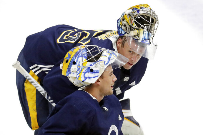 Nashville Predators goaltender Juuse Saros, bottom, and Pekka Rinne, top, both of Finland, talk during NHL hockey training camp Tuesday, July 14, 2020, in Nashville, Tenn. Predators coach John Hynes is making no commitments to either goaltender with the Predators just starting their first training camp with Hynes in charge. They open their best-of-five qualifying series against Arizona on Aug. 2 in Edmonton. (AP Photo/Mark Humphrey)