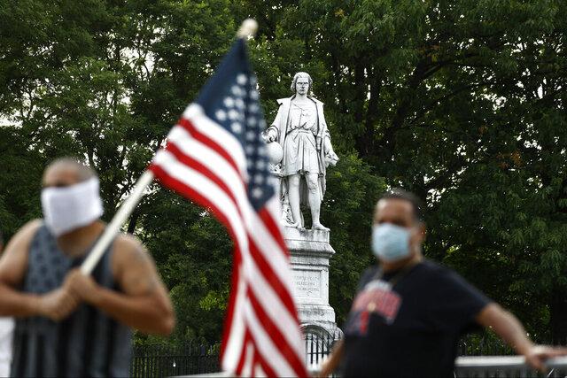 People gather near the statue of Christopher Columbus at Marconi Plaza, Monday, June 15, 2020, in the South Philadelphia neighborhood of Philadelphia. (AP Photo/Matt Slocum)