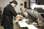 Chef Joseph Gattuso prepares a gyro sandwich in Schaumburg, Ill., on Sept. 6, 2019. He's working in the kitchen of Frato's Pizza, but filling an online order for the virtual restaurant Halal Kitchen. Frato's looks like a typical restaurant, but cooks there whip up dishes for four other restaurants at the same time. Thousands of restaurants are experimenting with virtual spin-offs, trying to capitalize on the rising popularity of online ordering. (AP Photo/Teresa Crawford)