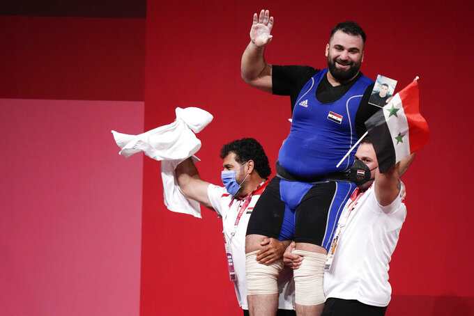 Man Asaad of Syria is lifted by his coaches after winning a bronze medal in the men's +109kg weightlifting event, at the 2020 Summer Olympics, Wednesday, Aug. 4, 2021, in Tokyo, Japan. (AP Photo/Luca Bruno)