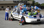 Melanie Dickey, a registered nurse for over 40 years, places an item on a makeshift memorial for Tulsa Police Officers Craig Johnson and Aurash Zarkeshan at Mingo Valley Division Tuesday, June 30, 2020. The officers were shot early Monday morning during a traffic stop. (Mike Simons/Tulsa World via AP)